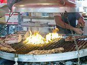 picture of brazier  - adding salt on roasted meat in large brazier in country fair - JPG
