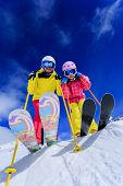 Ski, skiers, sun and winter fun - skiers enjoying ski vacation