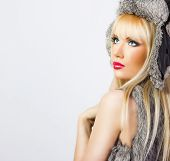 Beautiful Blonde Girl In Fur Hat On Grey Background