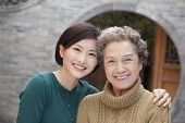 Grandmother and granddaughter in front of round arch