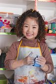 picture of medium-  length hair  - Girl wearing apron and playing with clay - JPG