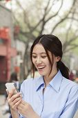 Young woman smiling and looking mobile phone