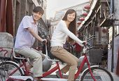 Side view of young couple on tandem bicycle in Beijing