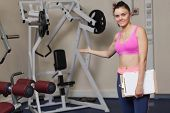 foto of lats  - Portrait of a smiling female trainer with clipboard pointing toward the lat machine in the gym - JPG