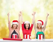 christmas, x-mas, winter, happiness concept - three smiling women in santa helper hats with gift box