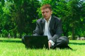 Businessman In A Park On The Grass Workin
