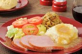 stock photo of biscuits gravy  - Closeup of a ham dinner with mashed potatoes gravy stuffing and a salad - JPG