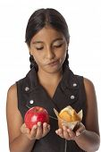 Young teenage girl with an apple and a muffin in her hands on white background
