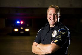 stock photo of police  - A smiling police officer with his patrol car in the background - JPG