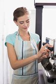 Portrait of a smiling female barista preparing espresso at coffee shop