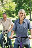 Portrait of beautiful woman with man riding bicycles together in a park