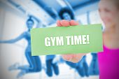Fit blonde holding card saying gym time against class in gym