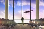 Rear view of mature businessman posing against airplane flying past departures lounge