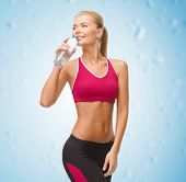 fitness, healthcare and dieting concept - smiling sporty woman with bottle of water