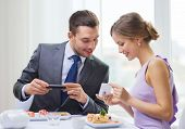 restaurant, couple, technology and holiday concept - smiling woman showing picture to husband or boy
