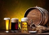 Beer glasses, old oak barrel and wheat ears on wooden table.