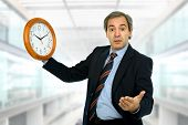 mature handsome businessman holding a clock at the office