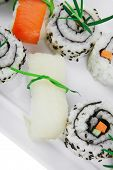 Maki Roll with Deep Fried Vegetables inside . on long white plate . isolated over white background .