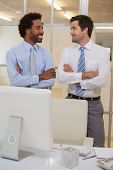 Two smiling young businessmen with arms crossed looking at each other in the office