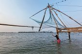KOCHI, INDIA - FEBRUARY 25, 2013: Local fisherman fishing with net near Kochi chinese fishnets. Fort