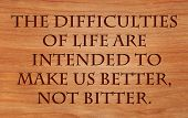 The difficulties of life are intended to make us better, not bitter - quote by unknown author on wooden red oak background