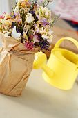 Beautiful bouquet and watering can on the table