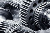 stock photo of gear  - gears and cogwheels set against brushed aluminum - JPG