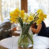 stock photo of lent  - Table in the cafe with lent lily and loving couple at background - JPG
