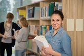 Smiling student holding books in front of bookshelf at library