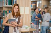 Smiling college student holding tablet with friends standing in library