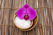 Pink orchid with salt in bowl on bamboo mat