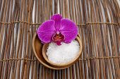 Macro of orchid with white salt on bowl on bamboo mat