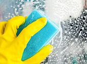 Hand in yellow protective glove cleaning glass with sponge