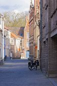 Two Bicycles Leaning Against Brick Buildings Bruges