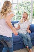 Excited mother looking at daughter in living room