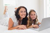 Portrait of mother and daughter with laptop lying in bed at home