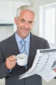 Smiling businessman having coffee in the morning before work at home in the kitchen