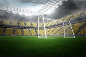 Large football stadium with lights and yellow fans