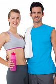 Portrait of a sporty young couple with water bottle and towel over white background