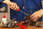 Repairman repairing parts of the old automotive engine