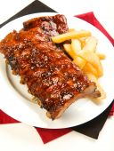 pic of baby back ribs  - Ribs with smoky spicy sauce accompanied by french fries - JPG