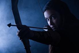 stock photo of archery  - Beautiful archery woman aiming smoky blue background - JPG