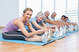 foto of senior class  - Happy female trainer with class stretching hands to legs at yoga class - JPG