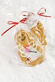 image of desert christmas  - Gingerbread girl cookie in clear bag on a festive Christmas snow background - JPG