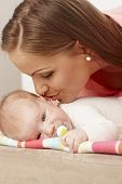 picture of teats  - Young mother kissing lying baby - JPG