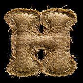 Linen or hemp vintage cloth letter H isolated on black background