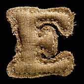 Linen or hemp vintage cloth letter E isolated on black background