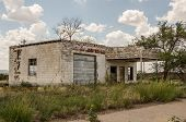 picture of neglect  - Neglected and abandoned former gas station and repair shop with a large crack in the building and lots of weeds in the yard on Route 66 - JPG