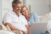 image of mature adult  - Portrait Of Happy Mature Couple Sitting On Couch Using Laptop - JPG
