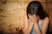 Teenage girl crying sitting on the floor with a grunge wall background